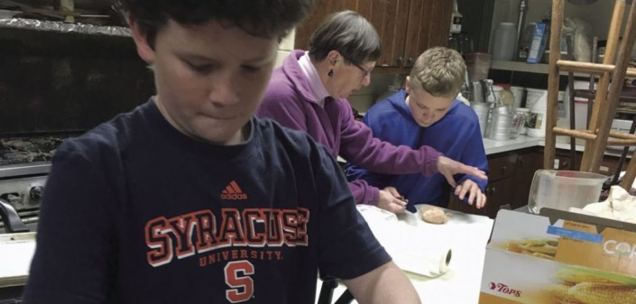 Boy cracking eggs into a bowl during cooking class.